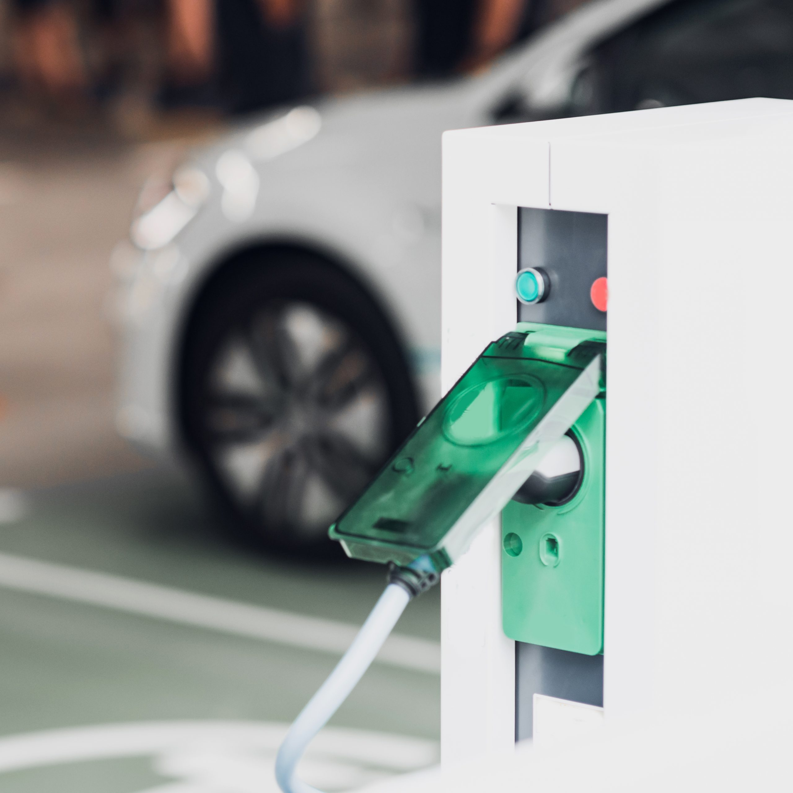 Electric vehicle charging station with EV in background