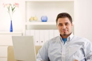 Man smiling near computer eager to learn about a precious metals IRA accounts