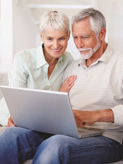 Wise Couple Investing In Gold IRA Accounts With Laptop Sitting Down.